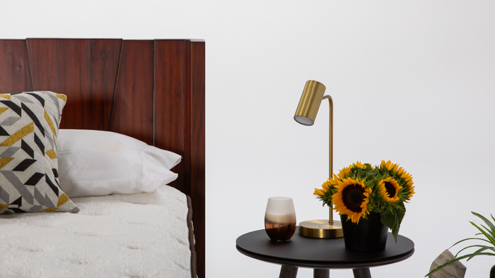 A photo showing the Barcelona wood bed with a side table and sunflowers